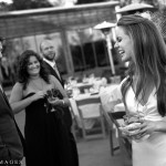 Bride laughing while groom and guest look on.