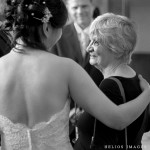 Bride talks with her new second mom while the groom looks on in the background in Winchester Town Hall in Winchester, MA.