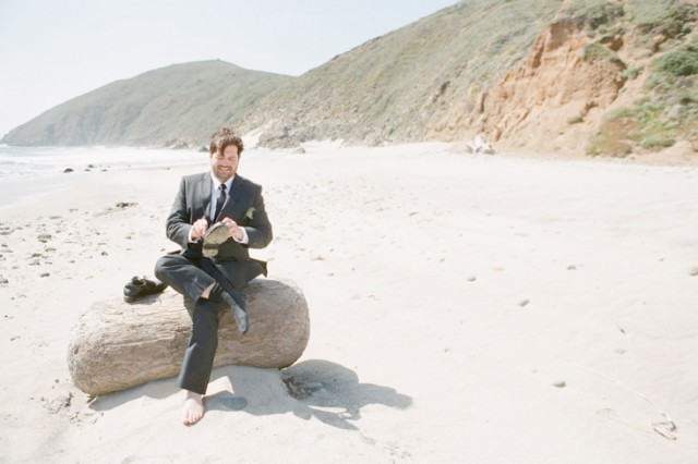 groom sitting on log at pfeiffer beach in big sur
