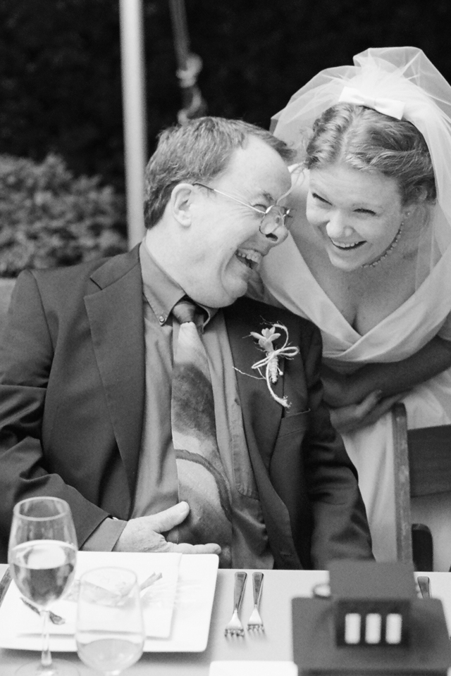 bride laughs hard with her dad at reception